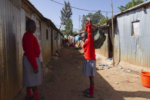 Two girls in school uniforms standing in a street in a slum